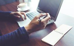 Maschio che lavora con la tazza di caffè e del computer portatile sulla tavola dello scrittorio in caffè Fotografia Stock
