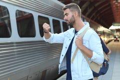 Maschio che mostra impazienza alla stazione ferroviaria Immagini Stock