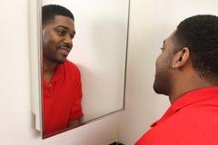 Maschio che osserva in specchio di vanità Fotografia Stock