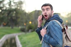 Maschio che ottiene le notizie scioccanti sul telefono all'aperto Fotografia Stock Libera da Diritti