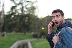 Maschio che ottiene nuovo scioccante sul telefono all'aperto Fotografie Stock Libere da Diritti