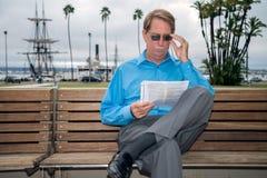Maschio che si siede su un banco che legge un documento Immagini Stock
