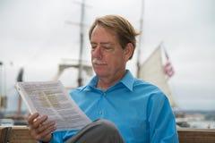 Maschio che si siede su un banco che legge un documento Immagine Stock