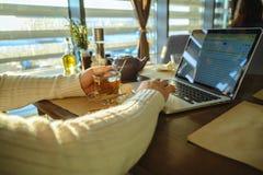 Maschio che sitiing nel tè bevente del caffe e che lavora al computer portatile Immagini Stock