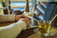 Maschio che sitiing nel tè bevente del caffe e che lavora al computer portatile Fotografia Stock