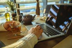 Maschio che sitiing nel tè bevente del caffe e che lavora al computer portatile Fotografie Stock