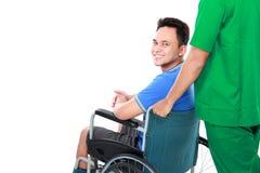 Maschio con il bracciolo ed il piede rotti facendo uso di sedia a rotelle immagine stock