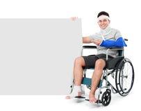 Maschio con la gamba rotta che si siede sulla sedia a rotelle con il segno Immagini Stock
