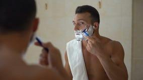 Maschio con schiuma sul fronte facendo uso del rasoio manuale per sistemare e radere barba in bagno video d archivio