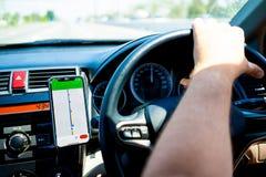 Maschio conducendo un'automobile sulla strada facendo uso di un nuovo, concetto di viaggio in macchina, gps immagini stock libere da diritti