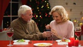 Maschio del pensionato che dà il contenitore di gioielli femminile sorridente, sorpresa di Natale, vigilia di festa stock footage