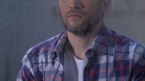 Maschio depresso solo che guarda nella finestra il giorno piovoso, difficoltà di vita, tristezza archivi video