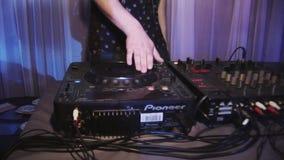 Maschio DJ che fila e che si mescola alla piattaforma girevole in night-club riflettori intrattenimento incoraggiare archivi video
