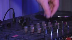 Maschio DJ che fila e che si mescola alla piattaforma girevole in night-club riflettori intrattenimento nightlife video d archivio