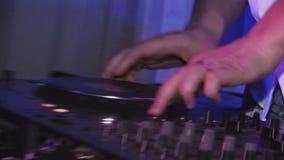 Maschio DJ che fila e che si mescola alla piattaforma girevole in night-club riflettori intrattenimento Partito di notte Suono archivi video