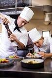Maschio e cuochi unici femminili che preparano alimento in cucina immagini stock