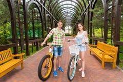 Maschio e femmina con le bici in arco Fotografia Stock Libera da Diritti