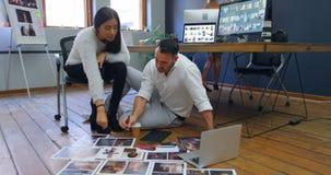 Maschio e grafici femminili che discutono sopra le fotografie 4k stock footage