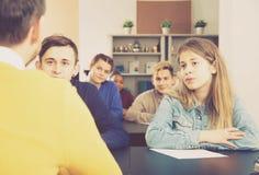 Maschio e studentesse concentrati dopo le spiegazioni di Fotografie Stock Libere da Diritti
