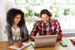 Maschio e studentesse sorridenti che si siedono alla tavola con il computer portatile Fotografie Stock