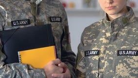 Maschio e studenti militari femminili che tengono i taccuini, istruzione dell'accademia, addestramento video d archivio