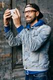 Maschio emozionante con la barba e baffi che portano la camicia d'avanguardia del denim con il gancio ed i jeans che guardano fel fotografia stock