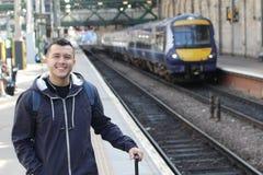 Maschio etnico sorridente che aspetta un treno immagini stock libere da diritti