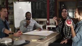 Maschio felice e colleghe millenari femminili di affari che sorridono mentre mangiando alimento sano Quattro hanno mescolato il c archivi video