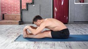 Maschio flessibile atletico che mostra ad esercizio di pratica d'allungamento perfetto di yoga vista laterale archivi video