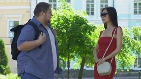 Maschio grasso che prova a parlare con ragazza esile graziosa, donna che lo trascura, insicurezze archivi video