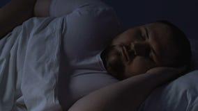 Maschio grassottello che lancia a letto, disordine medico, rottura del ciclo di sonno, insonnia stock footage