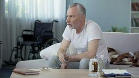 Maschio handicappato senior che si siede sul sofà e che prende le pillole, solitudine e tristezza video d archivio