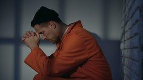 Maschio incarcerato caucasico che prega in cellula, ritenente colpevole e chiedente la pietà video d archivio
