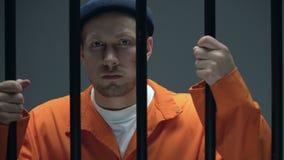Maschio incarcerato pericoloso con la cicatrice sul fronte che tiene le barre e che guarda alla macchina fotografica stock footage