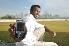 Maschio indiano asiatico che mostra il suo telefono che twittering Fotografie Stock Libere da Diritti