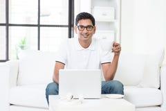 Maschio indiano facendo uso del computer a casa Fotografie Stock