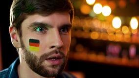 Maschio infelice con la bandiera tedesca dipinta sulla guancia che guarda TV, gioco perdente del gruppo immagini stock
