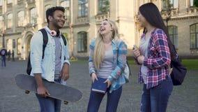 Maschio ispano divertente che scherza e che parla con le ragazze vicino all'istituto universitario, rottura, amici video d archivio