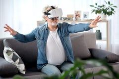 Maschio maturo felice divertendosi con il dispositivo del vr Immagine Stock