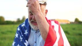 Maschio maturo in un cappuccio ed in un pensionato grigio della barba con la bandiera americana in parco il giorno soleggiato Fes archivi video