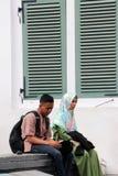 Maschio musulmano ed adolescenti femminili che si siedono insieme accanto alla finestra verde al quadrato in Città Vecchia, Jakar fotografia stock