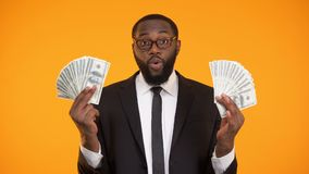 Maschio nero in occhiali che mostrano i mazzi di contanti, profitto, affare lucrativo archivi video
