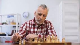 Maschio pensieroso invecchiante che gioca scacchi da solo, soffrendo solitudine nella casa di cura stock footage