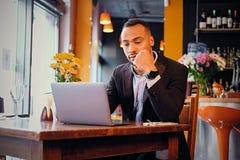 Maschio premuroso in un caffè facendo uso del computer portatile Fotografia Stock
