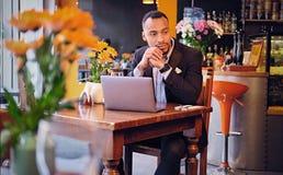 Maschio premuroso in un caffè facendo uso del computer portatile Fotografia Stock Libera da Diritti