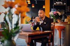 Maschio premuroso in un caffè facendo uso del computer portatile Fotografie Stock Libere da Diritti