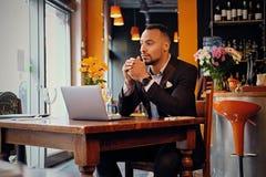 Maschio premuroso in un caffè facendo uso del computer portatile Fotografie Stock