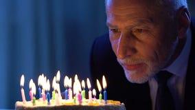 Maschio senior bello che esamina torta di compleanno che fa desiderio, celebrazione di festa video d archivio