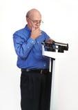 Maschio senior sulla scala del peso che sembra premurosa fotografia stock libera da diritti