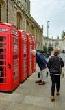 Maschio senior visto esaminare un contenitore antiquato e britannico di telefono a Cambridge, Regno Unito immagini stock libere da diritti